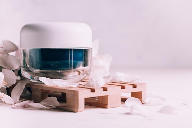 Niebieski szklany słoik kremu na drewnianym podium w formie palety na jasnej gipsowej powierzchni z kwiatami jabłoni, kopia przestrzeń