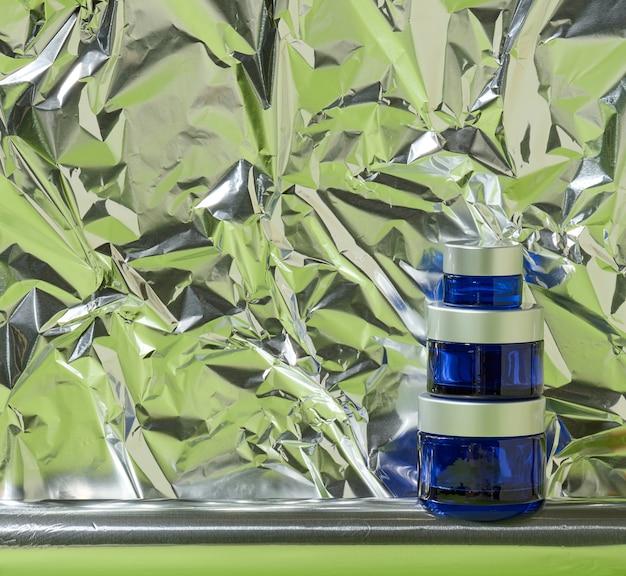 Niebieski szklany słoik z szarą plastikową pokrywką na kosmetyki na abstrakcyjnym tle z wymiętą folią. branding produktów kosmetycznych krem, maska, serum