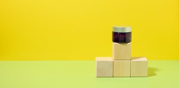 Niebieski szklany słoik z szarą pokrywką stoi na drewnianych kostkach, żółto-zielone tło. szablon do wyświetlania produktów kosmetycznych