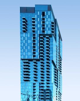 Niebieski szklany wieżowiec pod bezchmurnym niebem