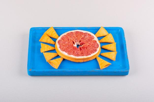 Niebieski talerz chipów trójkąta i plasterek grejpfruta na białym tle. zdjęcie wysokiej jakości