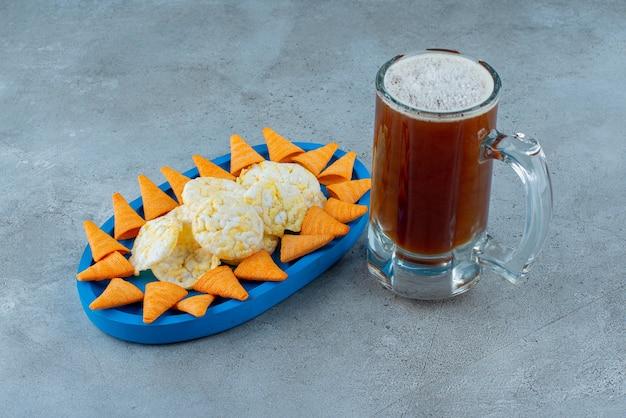 Niebieski talerz chrupiących chipsów ze szklanką piwa. zdjęcie wysokiej jakości