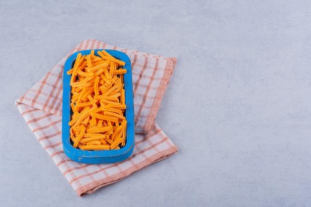 Niebieski talerz chrupiących chipsów ziemniaczanych na kamieniu.