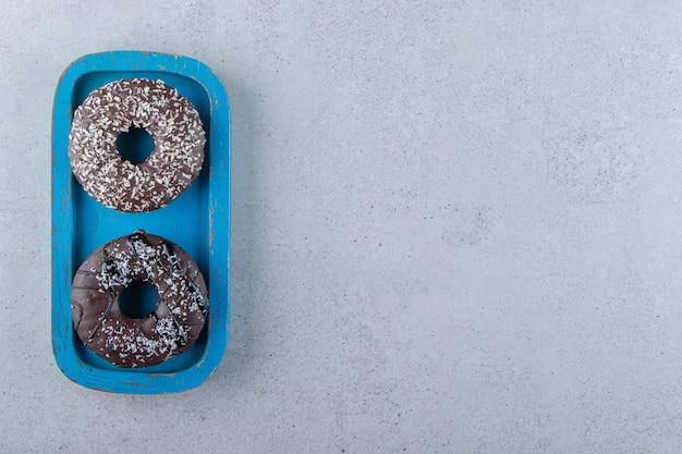 Niebieski talerz czekoladowych pączków na tle kamienia. zdjęcie wysokiej jakości