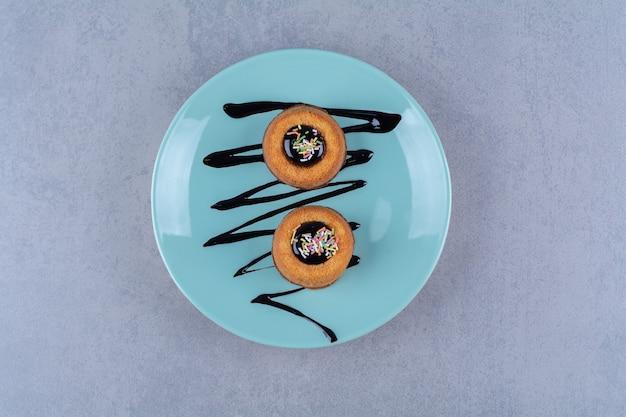 Niebieski talerz dwóch słodkich pączków z kolorową posypką.