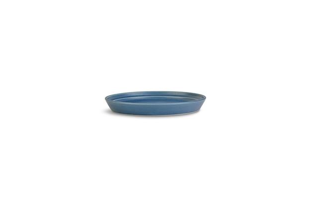 Niebieski talerz gliny pod światłami na białym tle