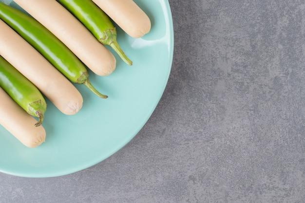 Niebieski talerz gotowanych kiełbasek z papryczkami chili.