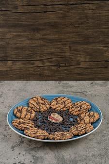 Niebieski talerz herbatników, czekolady i orzeszków ziemnych na marmurowym tle.