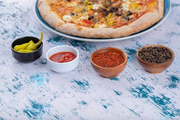 Niebieski talerz kiepskiej pizzy i papryki na marmurowym stole.
