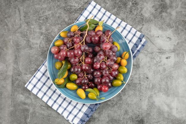 Niebieski talerz owoców kumkwatu i czerwonych winogron na powierzchni marmuru.