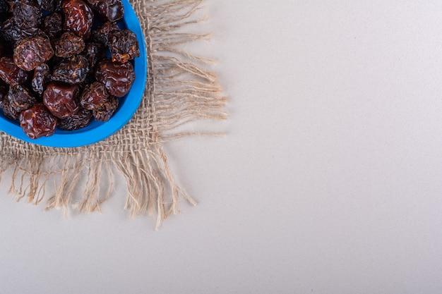 Niebieski talerz pełen suszonych smacznych śliwek na białym tle. zdjęcie wysokiej jakości