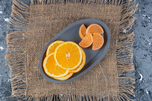 Niebieski talerz pokrojony w plasterki soczyste pomarańcze i słodkie marmolady na płótnie.