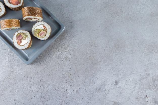 Niebieski talerz rolek sushi z tuńczykiem na kamiennym tle.