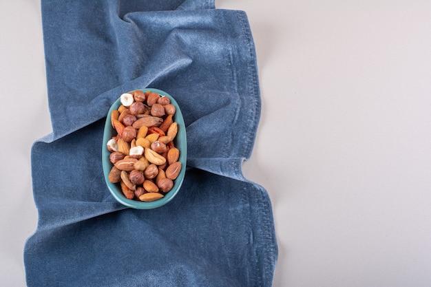 Niebieski talerz różnych orzechów organicznych na białym tle. zdjęcie wysokiej jakości