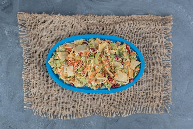 Niebieski talerz sałatki warzywnej na kawałku materiału na marmurowej powierzchni.