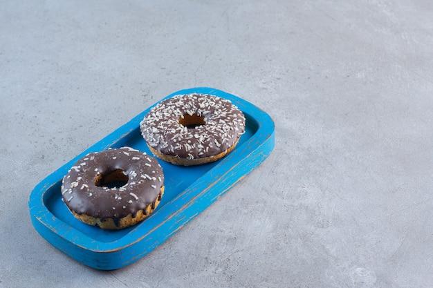 Niebieski talerz smacznych pączków czekoladowych na kamieniu.