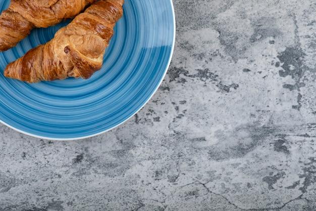 Niebieski talerz świeżych rogalików czekoladowych na kamiennej powierzchni.