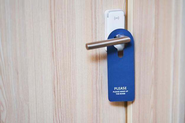Niebieski talerz wiszący na klamce pokoju hotelowego