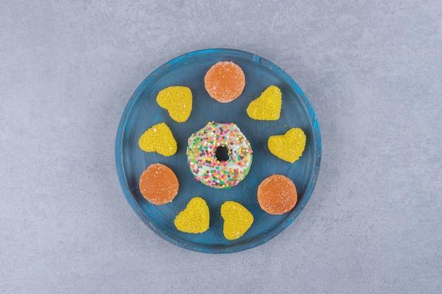 Niebieski talerz z małym pączkiem i różnymi marmoladami na marmurowej powierzchni