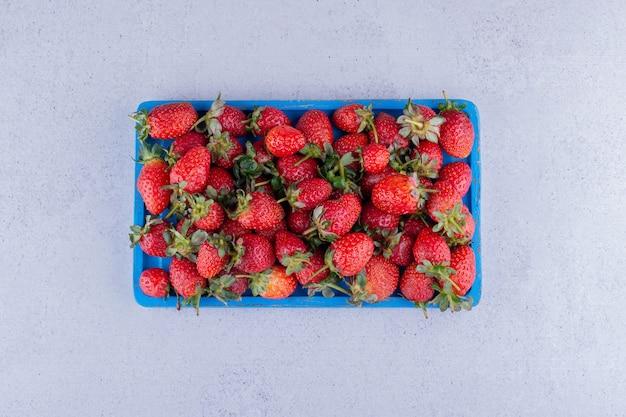 Niebieski talerz z porcją truskawek na marmurowym tle. zdjęcie wysokiej jakości