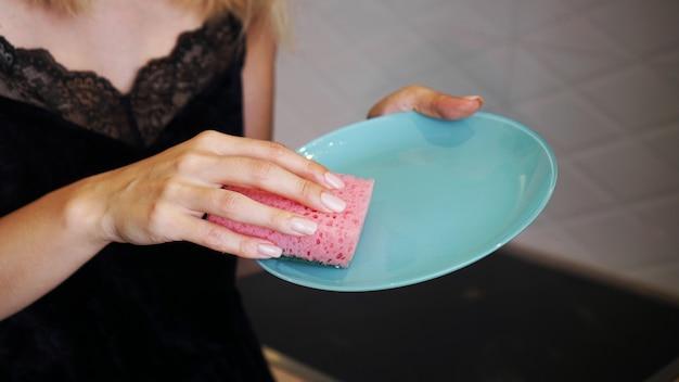 Niebieski talerz z różową gąbką do naczyń w dłoni na rozmytym tle kuchni