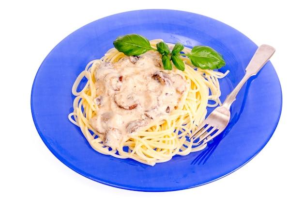 Niebieski talerz ze spaghetti i sosem grzybowym.