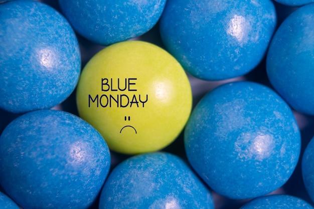 Niebieski tekst poniedziałek ze smutną buźką. jeden żółty cukierek w kolorze niebieskim. najbardziej przygnębiający dzień w roku. koncepcja niebieski poniedziałek. wpływ środowiska.