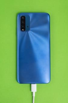 Niebieski telefon komórkowy podłączony do kabla usb - ładowanie