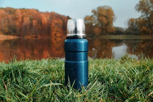 Niebieski termos próżniowy na zielonej trawie, jesiennym lesie i jeziorze.