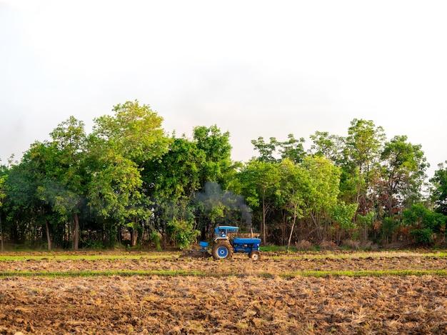 Niebieski traktor pracujący w gospodarstwie. niebieski traktor przygotowuje ziemię z kultywatorem rozsadnikowym prac rolniczych na polach uprawnych na zielonym drzewie i niebie.