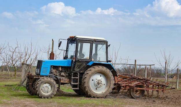 Niebieski traktor z kultywatorem w ogrodzie.