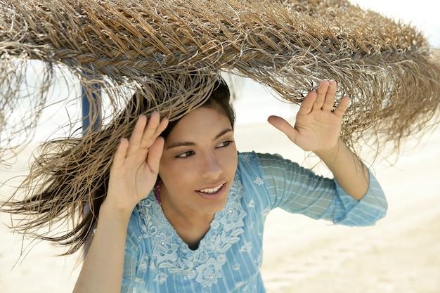 Niebieski ubrany portret kobiety, parasol plażowy