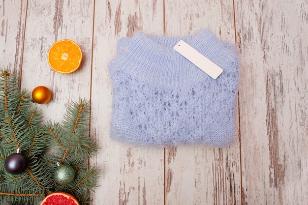 Niebieski wełniany sweter z metką na drewnianym tle. cytrusy, świerkowe gałęzie z ozdób choinkowych