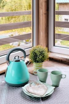 Niebieski żelazny czajnik zielony stół kubek niebieski zielony śniadanie kosz serce okno
