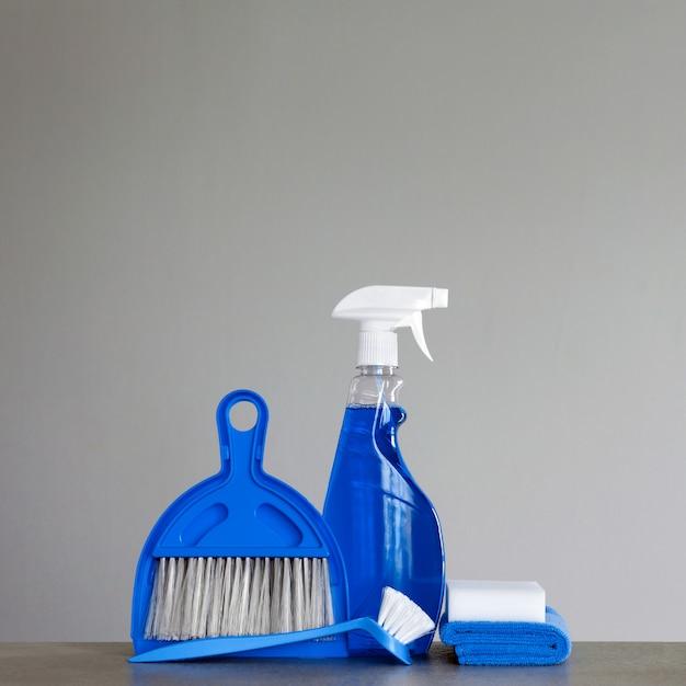 Niebieski zestaw do czyszczenia: środek czyszczący w sprayu, szczotka do mycia naczyń, ściereczki do kurzu, gąbka, miarka i miotła. copyspace.