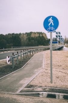 Niebieski znak drogowy ścieżki rowerowej i pieszej na białorusi. znak zamontowany na moście.