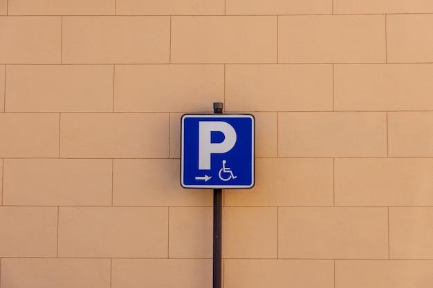 Niebieski znak wskazujący na parkowanie dla osób niepełnosprawnych na tle cegły