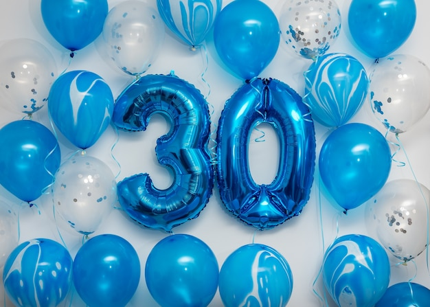 Niebieskie balony foliowe numer 30 z balonami helowymi na białym tle.
