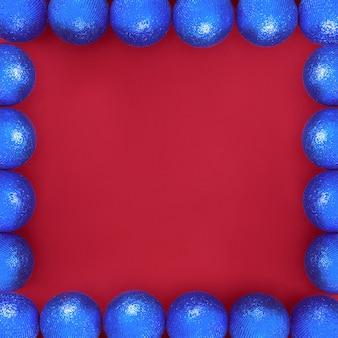 Niebieskie błyszczące bombki choinkowe na czerwonym tle w formie ramki wokół krawędzi na życzenia i kartki świąteczne.