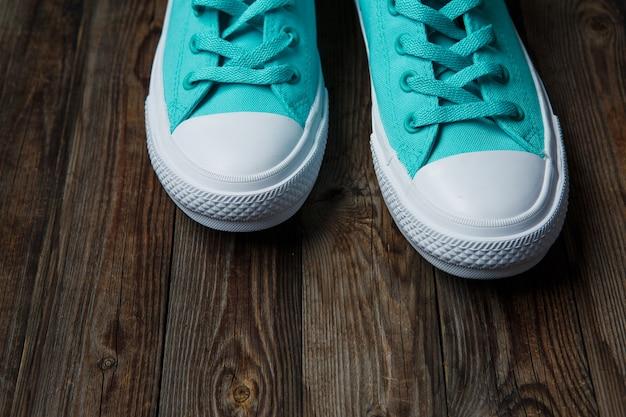 Niebieskie buty na pustej drewnianej podłodze