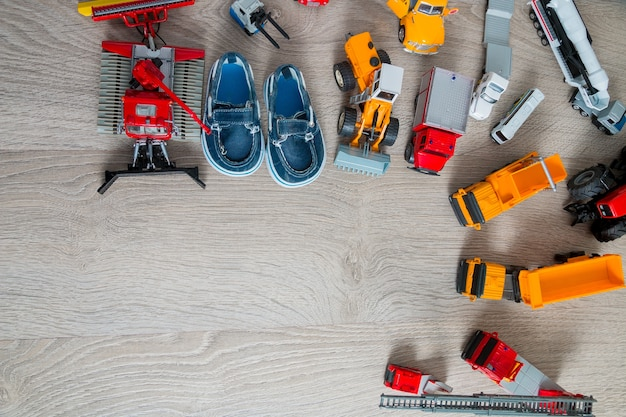 Niebieskie buty żeglarskie dla chłopca w pobliżu zestawu zabawek samochodowych. widok z góry. rama. skopiuj miejsce. leżał na płasko.