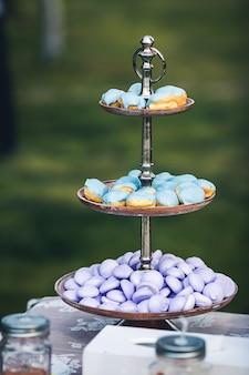 Niebieskie ciastka i fioletowe makaroniki na pięknej metalowej podstawce.