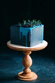 Niebieskie ciasto ozdobione jeżynami i jagodami.