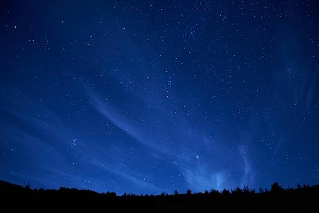 Niebieskie ciemne nocne niebo z wieloma gwiazdami. tło