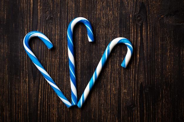 Niebieskie cukierki laski na ciemnym tle drewnianych