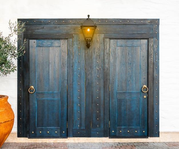 Niebieskie drewniane drzwi z pozłacanymi uchwytami pierścieniowymi i świecącą lampą uliczną, vintage design wejścia do budynku.