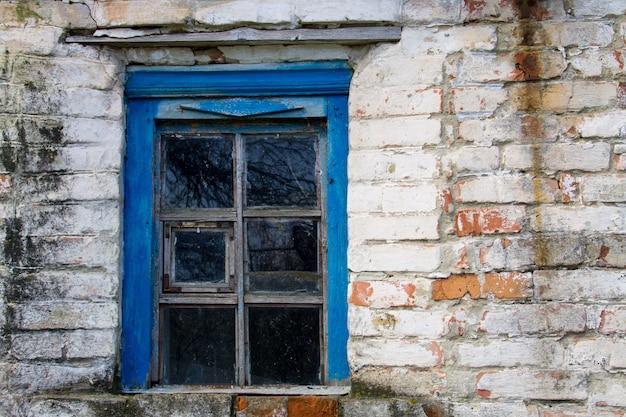 Niebieskie drewniane okno w starym ceglanym murze