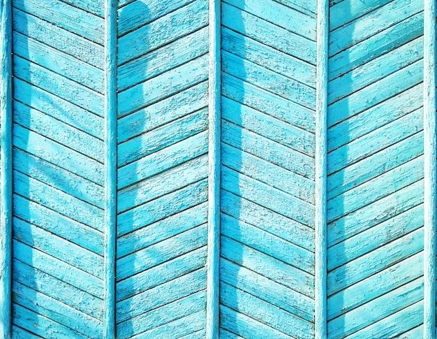 Niebieskie drewno teksturowanej tło. drewniana ściana lub ogrodzenie z zygzakowatymi deskami. jednolity wzór w jodełkę