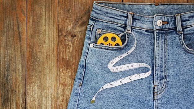 Niebieskie dżinsy i miara. koncepcja wyszczuplania lub szycia denim. dżinsy na drewnianym tle