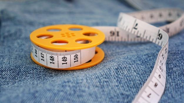 Niebieskie dżinsy i miara. koncepcja wyszczuplania lub szycia denim. taśma miernicza w żółtej szpuli na denimowym tle